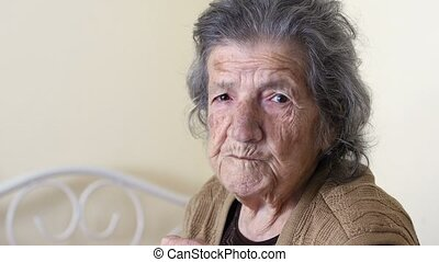 """ old woman eating, looking camera at home"""