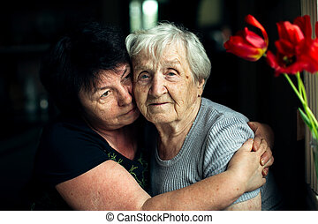 Old woman embrace with her adult daughter.