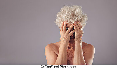 Old woman feeling shy - Portrait of shirtless old lady...