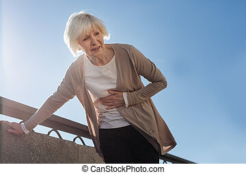 Old woman feeling stomachache outside - It can happen...