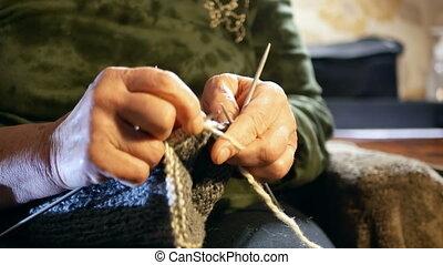 Old woman garments - The old woman sits at home and knits...