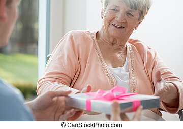 Old woman giving present her care assistant