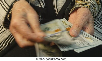 Old woman hands counting hundred dollar bills