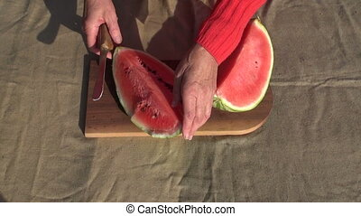 old woman hands cutting watermelon