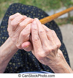 Old woman hands holding a walking cane outdoors