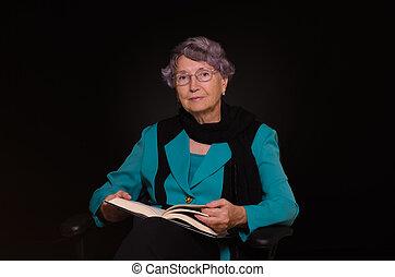 Old woman holding a book in her lap and looking straight