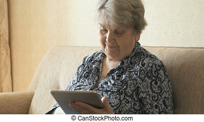 Old woman holding a digital tablet and view photos