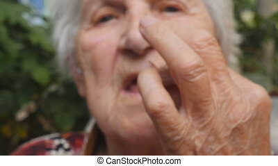 Old woman holding white pill in her hand and take it. Grandmother putting tablet in her mouth. Healthcare and medical concept. Close up Slow motion