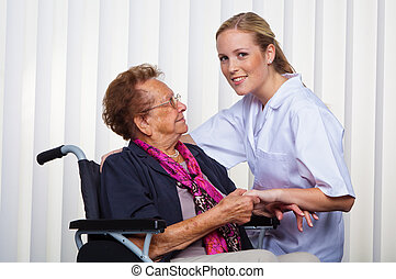 old woman in a wheelchair and a nurse
