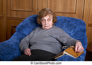 old woman in an armchair and  the book