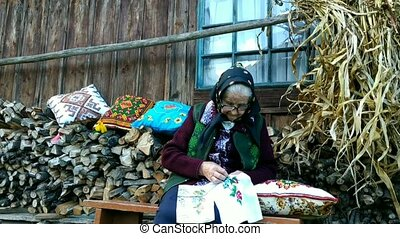 Old woman in ethnic clothes sitting near her wooden country house Creating ukrainian embroidery.