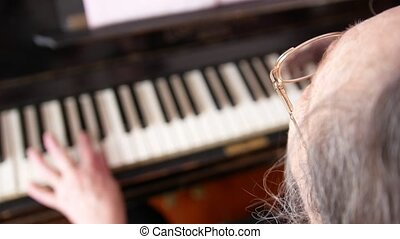 Old woman in eyeglasses is playing the piano