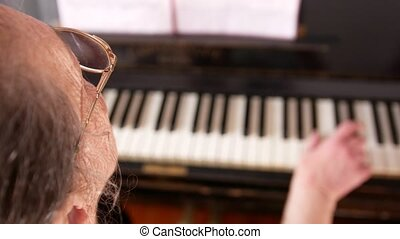 Old woman in eyeglasses is playing the piano - Old woman in...