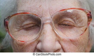 Old woman in eyeglasses looking into camera. Eyes of an elderly lady with wrinkles around them. Close up portrait of grandmother. Slow motion
