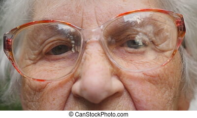 Old woman in eyeglasses looking into camera. Close up...