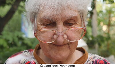 Old woman in eyeglasses reading something and smiling...