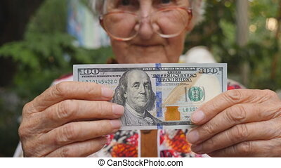 Old woman in eyeglasses showing bill of one hundred dollar into camera and smiling outdoor. Granny holding cash outside. Money concept. Close up Slow motion