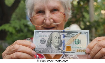 Old woman in eyeglasses showing one hundred dollar bill into camera and smiling outdoor. Happy grandmother holding foreign currency outside. Money concept. Close up Slow motion