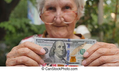 Old woman in eyeglasses showing one hundred dollar bill into...