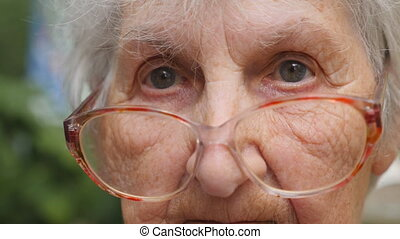 Old woman in eyeglasses turning her head and looking into...