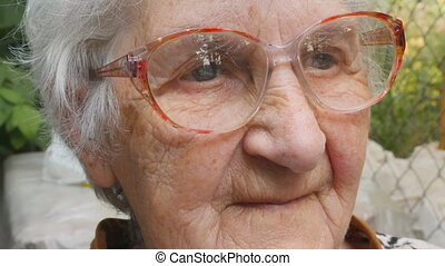 Old woman in glasses looking forward and smiling. Portrait...