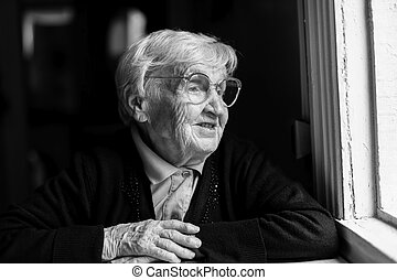 Old woman in glasses sitting by the window in the house.