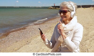 old woman in headphones with smartphone on beach -...