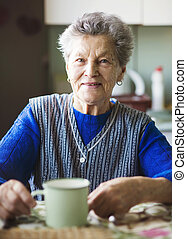 Old woman in the kitchen - Old woman is drinking tea in her...