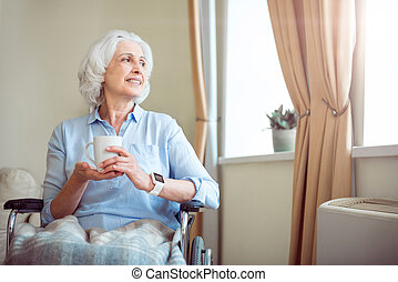 Old woman in wheelchair holding cup