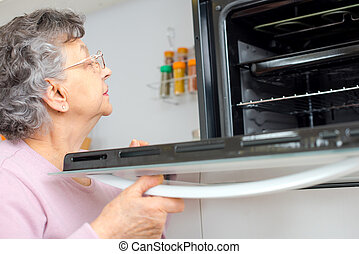 old woman inspecting the oven