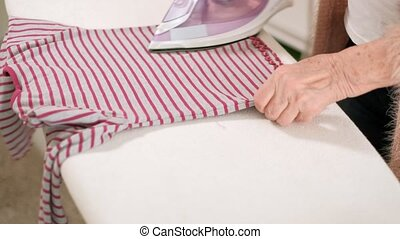 old woman ironing clothes at home