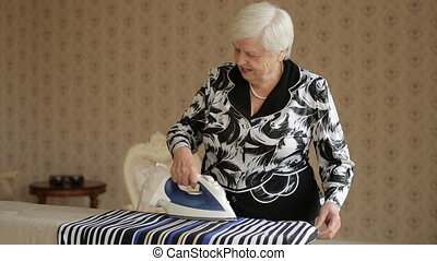 Old Woman Ironing Clothes - Elderly woman ironing clothes at...