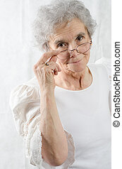 old woman is looking over her glasses