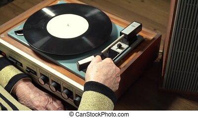 Old woman listening vinyl record on player - Senile women...
