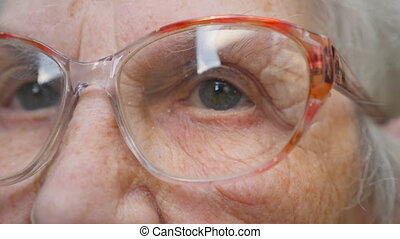 Old woman looking into the distance and taking off glasses....