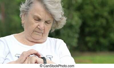 Old woman looks at a wristband fitness tracker
