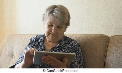 Old woman looks at pictures using a digital tablet