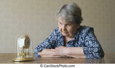 Old woman looks at the table clock with pendulum