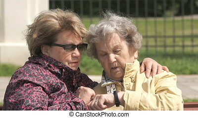 Old woman looks at wristband fitness tracker - Two women sit...