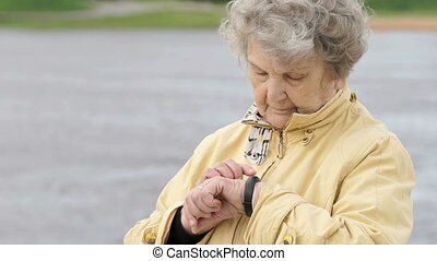 Old woman looks at wristband fitness tracker