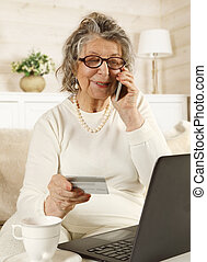 Old woman makes an order online using a credit card