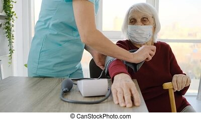 Old woman measuring blood pressure using tonometer during appointment with doctor