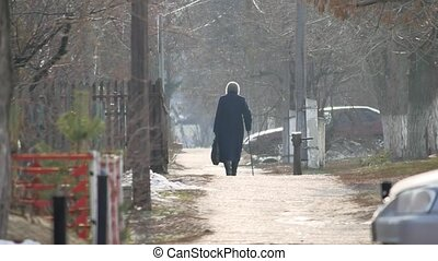 old woman pensioner grandmother is in a coat and scarf in...