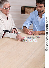 old woman playing cards with young man