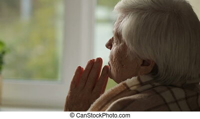 Old woman praying in a fron of window - Old woman with deep...