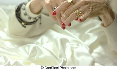 Old woman putting on ring on finger. Elderly woman with...