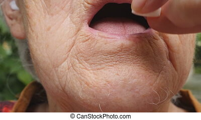 Old woman putting white pills in her mouth. Grandmother taking tablets that alleviate her health issues. Healthcare and medical concept. Close up Slow motion