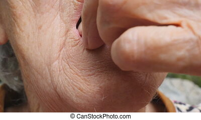 Old woman putting white pills in her mouth. Grandmother...