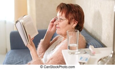 Old woman reading a book on the couch at home