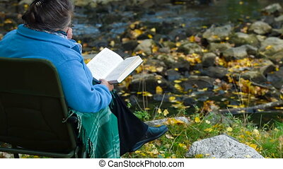old woman reading  book in autumn